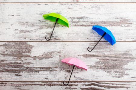 Colorful mini umbrellas on white wooden background